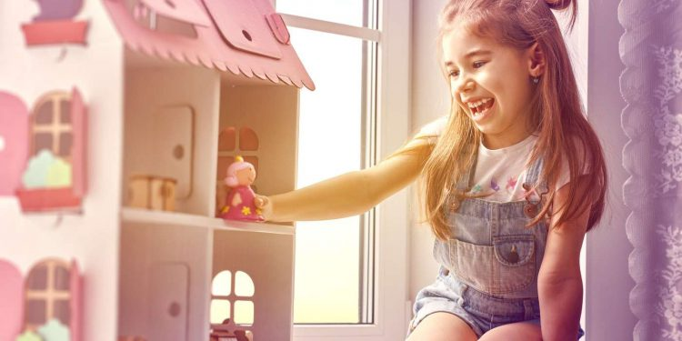 girl happily playing on her dollhouse