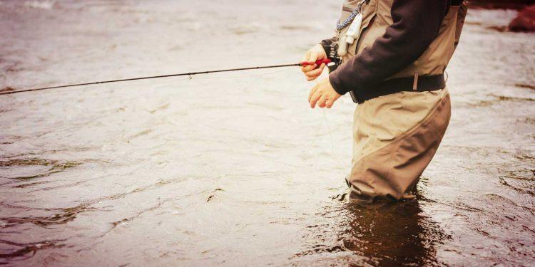 man in the water wearing waders