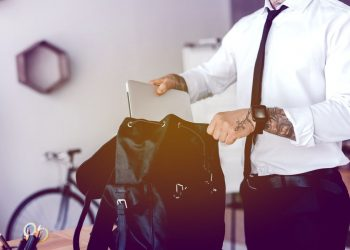 adult man with a tattooed arm and a smart watch wearing a business attire and placing his laptop inside a black backpack