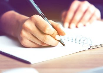 womans hand writing on a spiral notebook