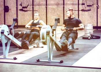 man and woman in black gym gear using row machines in the gym