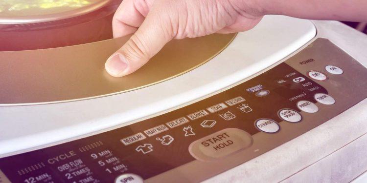 adult hand opening a washing machine