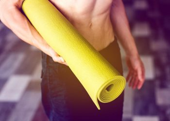 fit adult man holding a yellow yoga mat under his arm