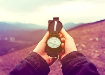 woman searching direction with a compass in the mountains.