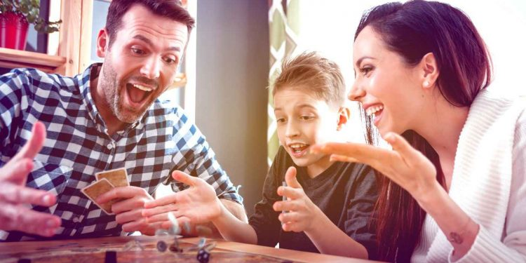 Happy family playing a board game at home,