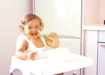 laughing child sitting on a high chair while holding a spoon