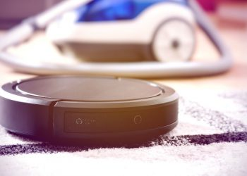 Robotic vacuum cleaner working on a carpet with traditional vacuum on the background