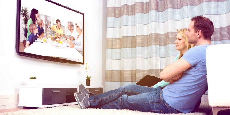 Couple Sitting On Carpet Watching Television