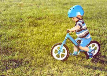 A boy in helmet riding a blue balance bike