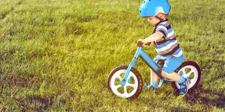 A boy in helmet riding a blue balance bike