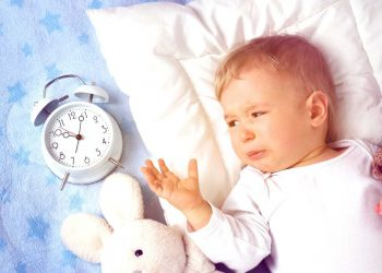 baby lying in bed with alarm clock and crying