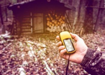 Man the hunter with a GPS navigator in the forest