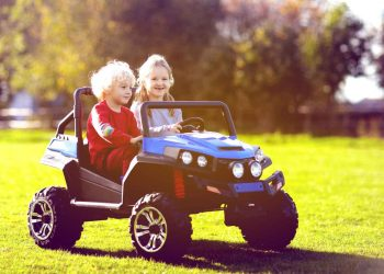 Little boy and girl happily riding a toy truck in the garden
