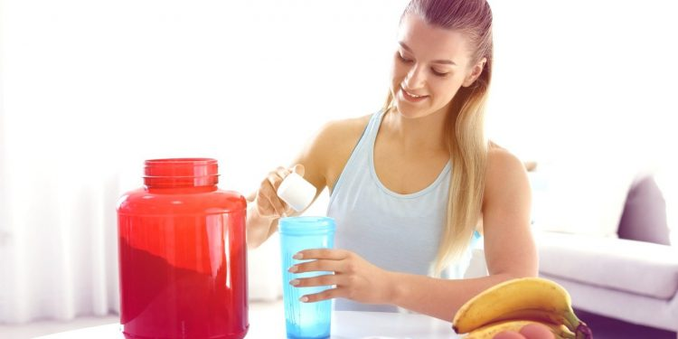 Young woman preparing protein shake at table