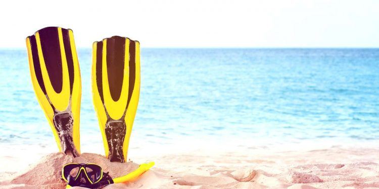 a yellow mask with tube for snorkeling and a pair of yellow diving fins in a sand