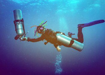 Scuba diver holding two scuba tanks under the sea