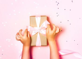 Child hands holding beautiful gift box on pink background, with sparkling glitter around
