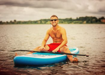 male sitting on a blue inflatable SUP