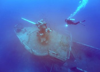 ship wrecked under the sea with a scuba diver observing using a diving light
