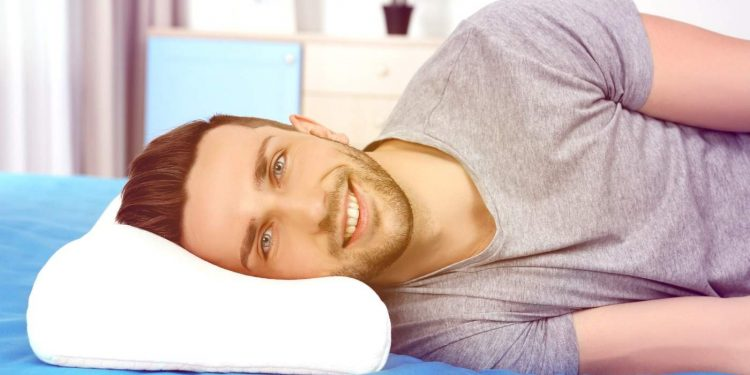 Young man lying on bed with orthopedic pillow smiling