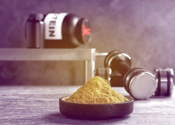 protein powder in bowl and dumbbells on table
