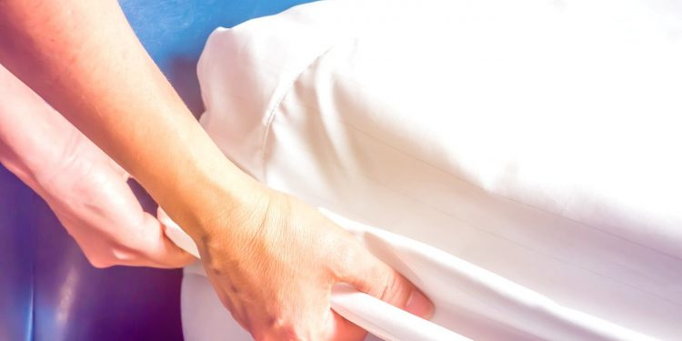 woman's hand putting a white mattress on the bed