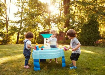 kids playing on a water table outside